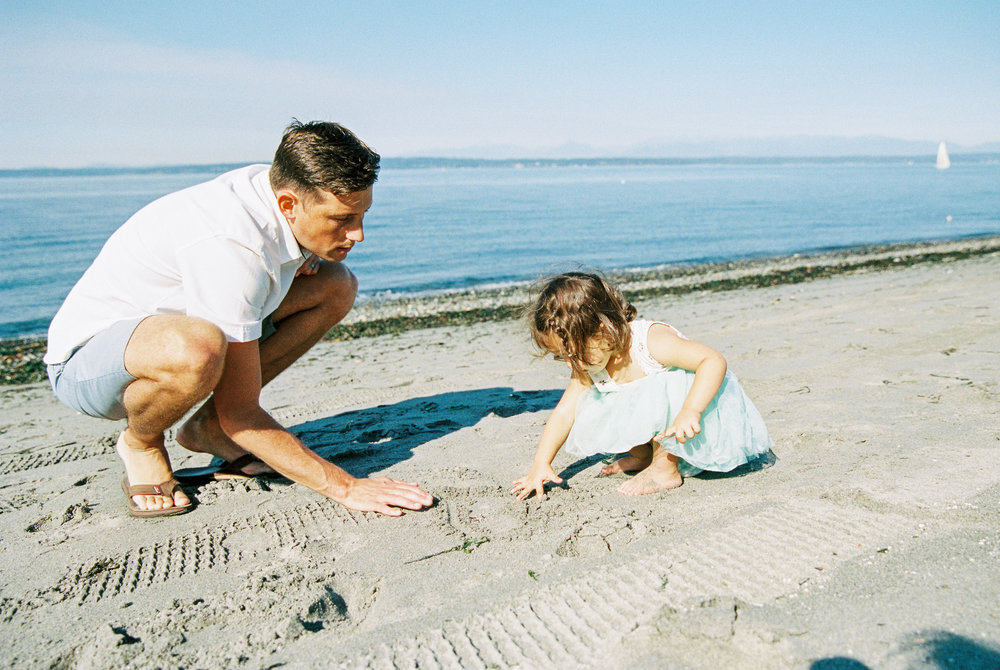 Seattle family film photographer photos photo girl daughter mom dad ocean pudget sound waves sand driftwood light sun newborn new born daddy daughter writing in the sand