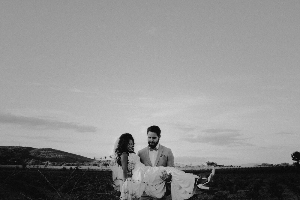 bride groom carrying bride across wine field in tuscany by mark hadden amsterdam wedding photographer