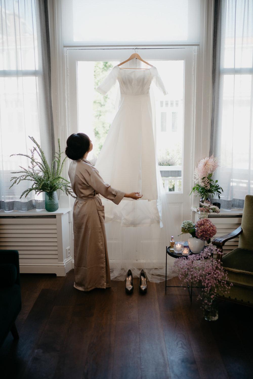 prachtige trouwjurk gefotografeerd tijdens het klaarmaken van de bruid