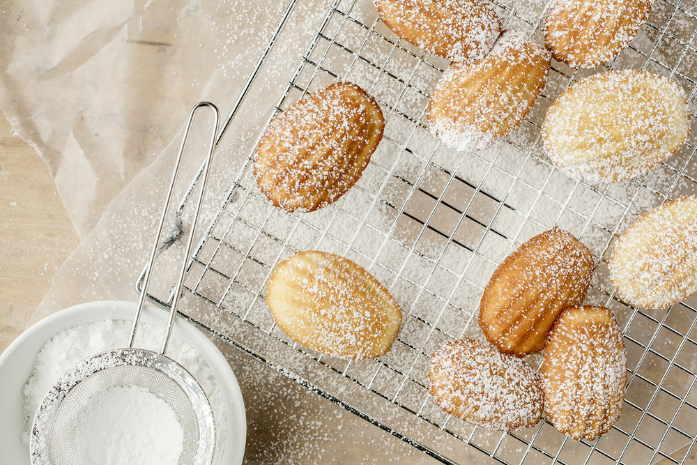 Madeleines dusted with powdered sugar....minus one.