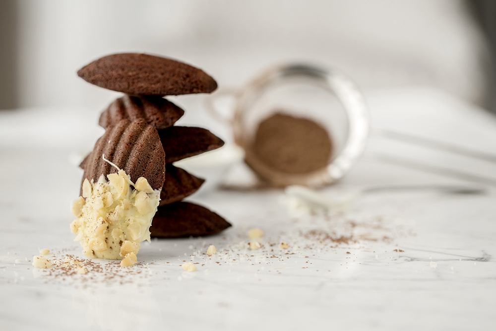 Chocolate Madeleines with white chocolate, crushed macadamia nuts and dusted with cocoa.