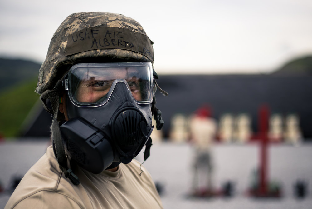 An Airman prepares to fire for qualification, fitting his gas mask. Airman First Class Alberto-Lopez, Camp Hansen, Okinawa, Japan