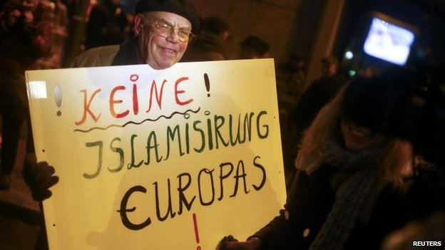 "A German PEGIDA supporter holds a sign that reads, ""No Islamization of Europe."""