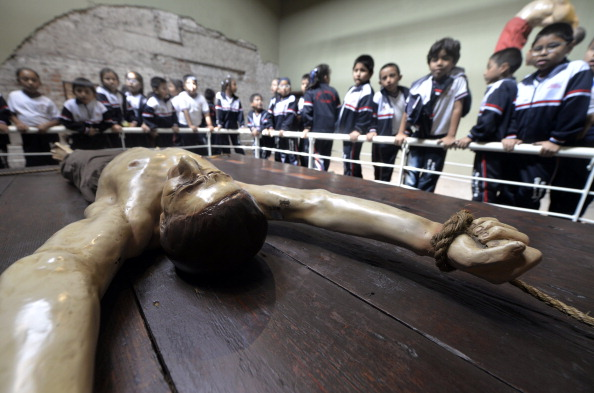 School children peer over at a wooden representation of a victim of the Inquisition in Lima, Peru.
