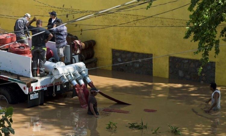 Bomberos conectan bomba de agua en zona inundada de Cihuatlan | Foto: AFP
