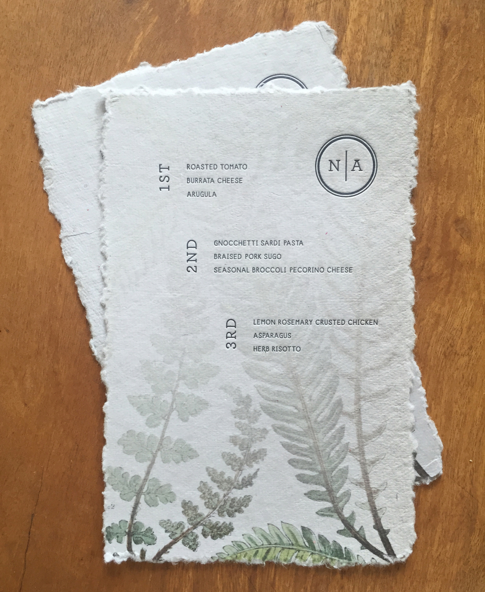Menu with hand-torn edges and a botanical fern print