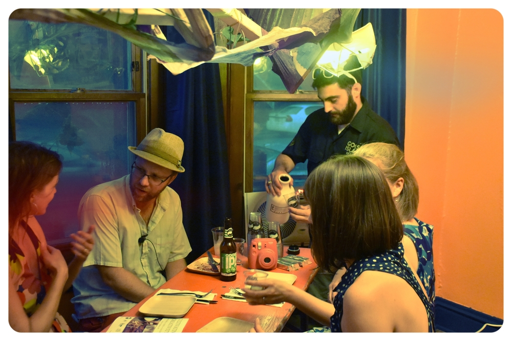 Erika Jones, Executive Director of FairShare CSA (left) converses with Artist Jeremy Wineberg (right). Robby Zahm from Goose Island serves samples of  Goose Island Bee Squad .