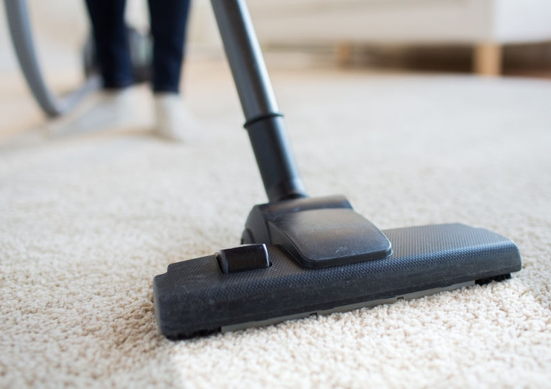 A woman cleaning a carpet
