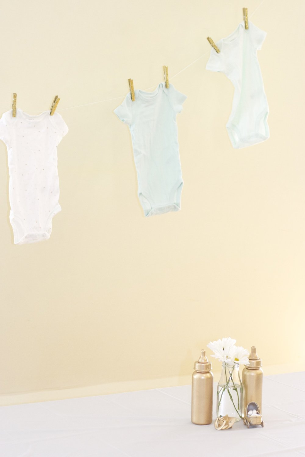 I took mint and white onesies from Target and some gold glitter clothespins to decorate the bare walls.