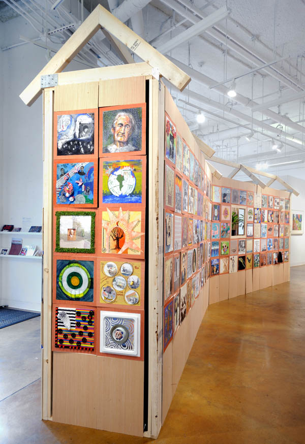 "GALLERY ATHE ONE HOUSE PROJECT220 artists stand up for tolerance, inclusion and unity.A project of the ArtWatch collective.Led by Ellyn Weiss and Jackie Hoysted.Exhibition supported by the Touchstone Foundation for the Arts - Over 220 artists have come together to demonstrate the power of visual communication to support true democratic values of tolerance, inclusion and openness and to resist efforts to divide us by race, gender, sexual preference, class or region. The vision of One House is for a country where we stand together.  Each artist contributed a 12"" square panel dedicated to an ancestor who came to this country -  voluntarily or involuntary - or was here before the arrival of the Europeans. A structure erected in the Touchstone Gallery will be covered entirely by those panels, representing the remarkable range of diverse humanity who have combined to make the strength of America. press release"