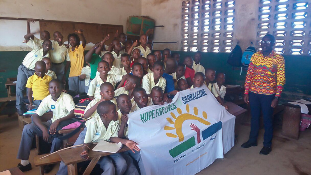 Boys class with hand painted banner of the Hope for Lives logo