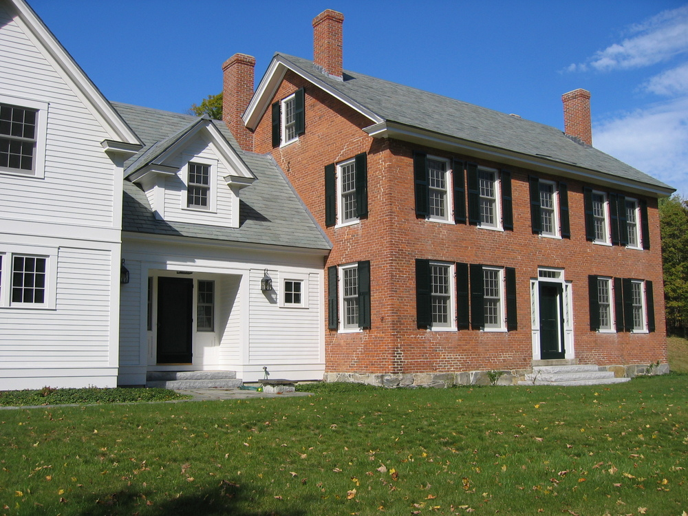 The primary living space is now located in the center ell and is easily accessed from the barn/garage.  A first floor master suite was located at the opposite end, in the original living space of the brick house.