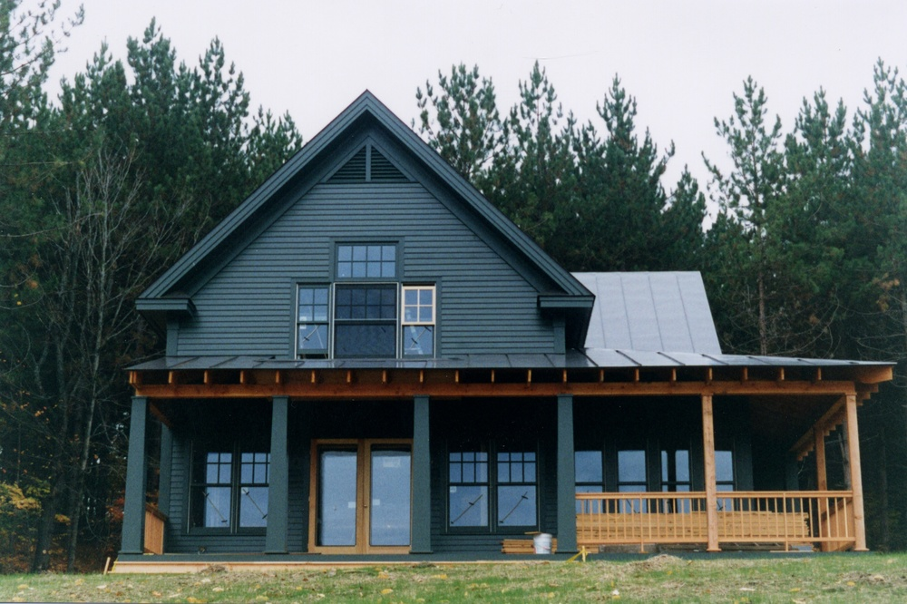 The house makes use of a compact floor plan that includes three bedrooms, an open plan on the first floor, and porches that allow interior spaces to expand to the outdoors.