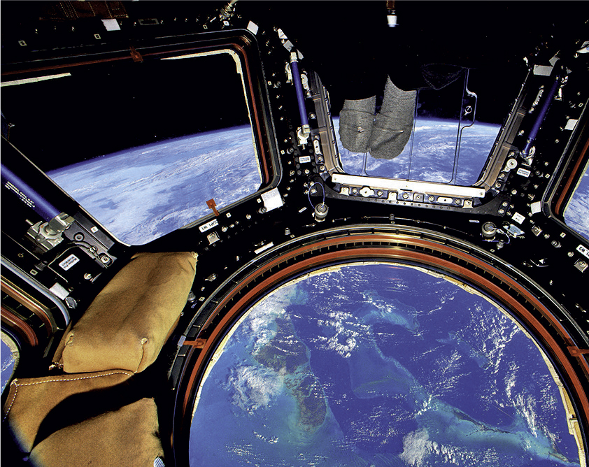 Earth seen from the Space Station Cupola, where Michael Hopkins (inset), would go to receive Communion