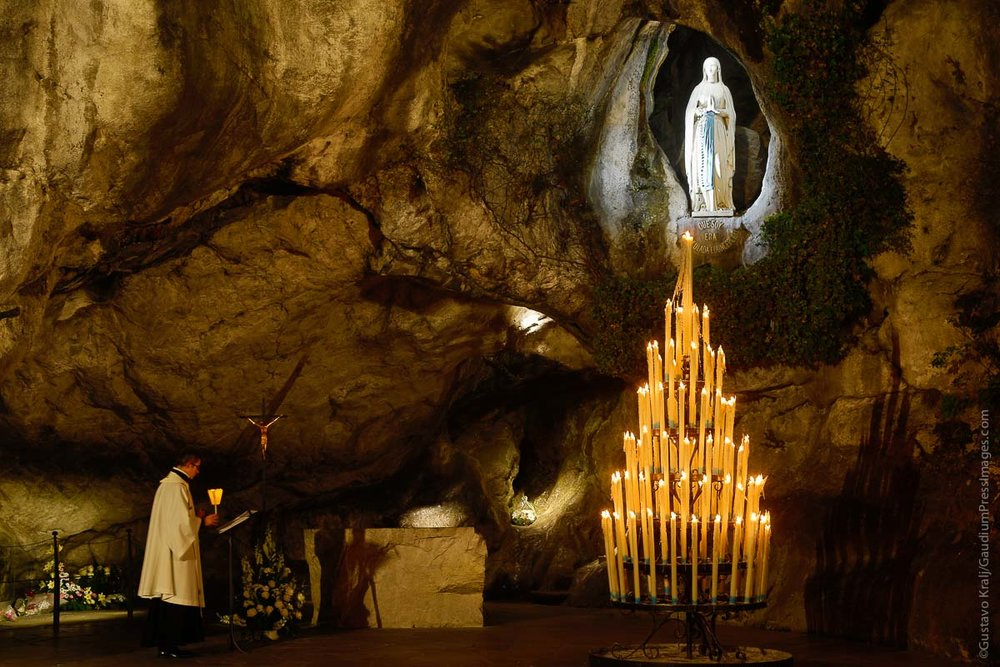 Lourdes, France: Pilgrims pray and burn Candles at the Grotto of the apparitions of Our Lady to St Bernardette Soubirous. Photo: gustavo Kralj/GaudiumpressImages.com