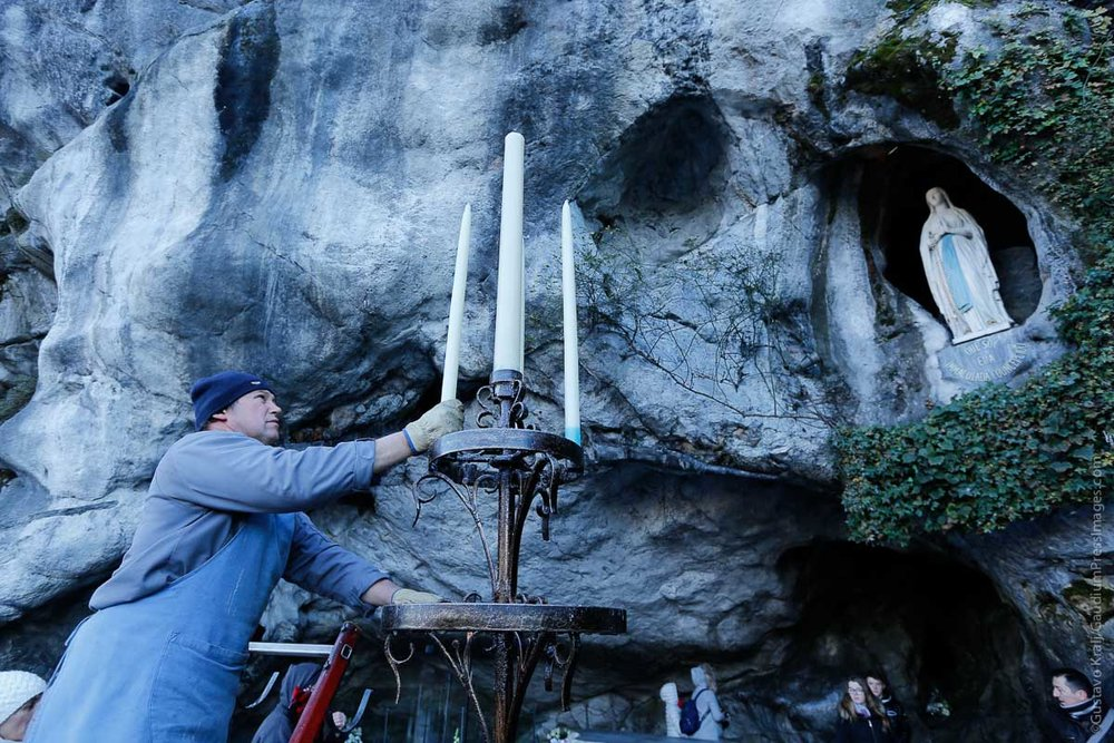 Lourdes, France: Michel, a worker or 35 years at the Shrine, changes the candles at Grotto of the apparitions of Our Lady to St Bernardette Soubirous. Photo: gustavo Kralj/GaudiumpressImages.com