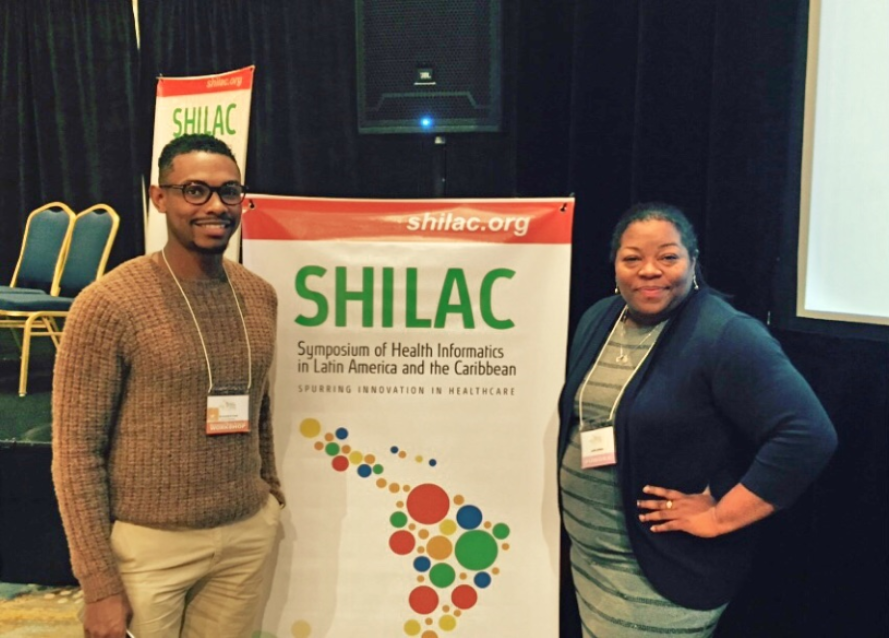 Research Associates Christopher Cross and Latifa Jackson pose in front of the SHILAC poster.