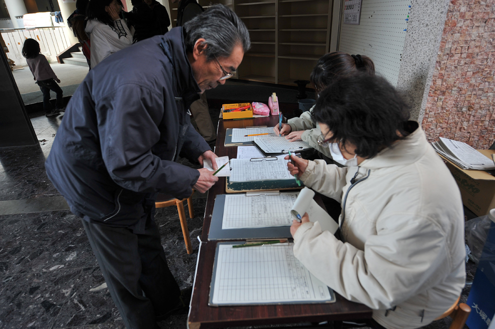 Japan: One Week Later    A man looks for a relative at a community center  used as a shelter in the tsunami-damaged town of Otsuchi on March 18.   (Nicholas Kamm/AFP/Getty Images)    (via  Boston.com )