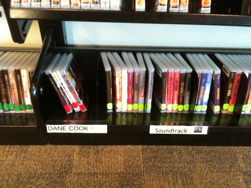 """valeriek: Two of the """"genres"""" available in the audio section of the Silver Lake Library. Now, who's going to change that label from DANE COOK to """"COMEDY?"""" Where's my label maker…. Someone make this happen."""