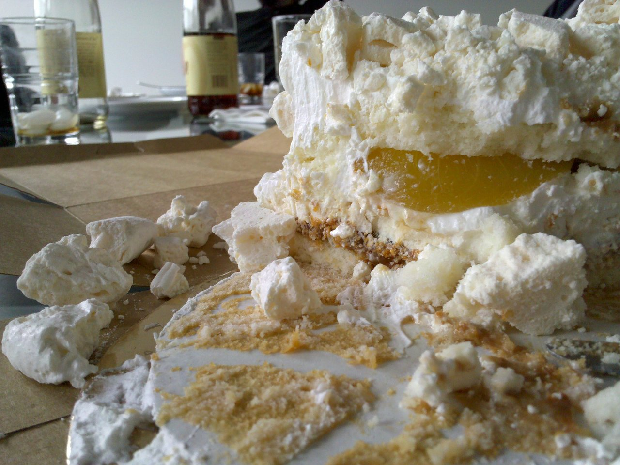 Remains of a cake filled with dulce de leche and peaches, covered in merengue crumbles and fresh whip cream.