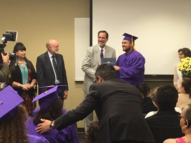 Neery Velazquez accepts his diploma from Arwyn Wild, Executive Director of San Manuel Gateway College, Loma Linda University.