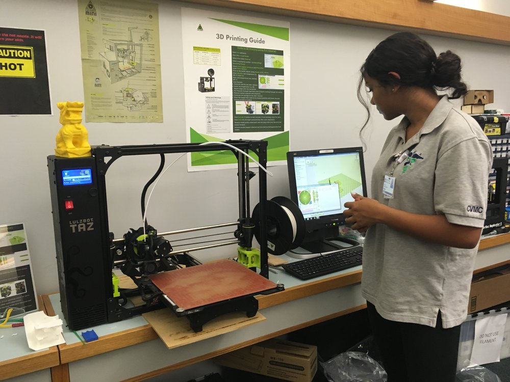 Maya Dessai waits for the 3D printer to make a portion of her robot.