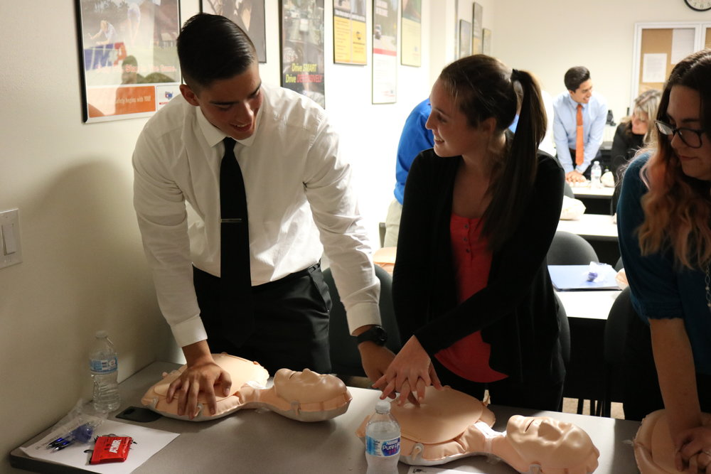 Students practice proper technique for hands-only chest compressions.