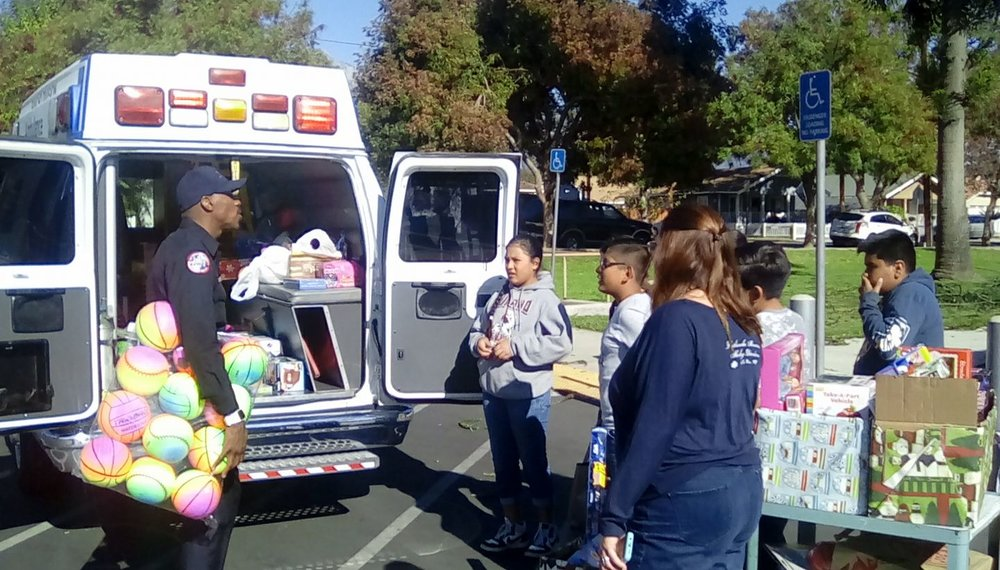 Travon McMillan greets students as they bring cartloads of toys out to the the ambulance.