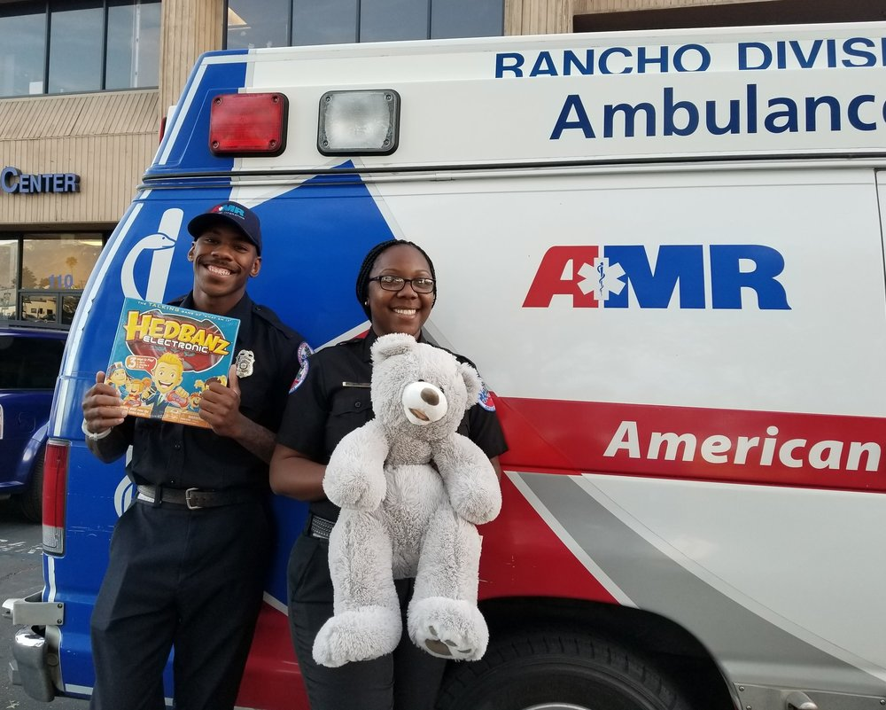 [L to R] EMT's Travon McMillan and Shalon Watkins unloading toys at Reach Out offices.