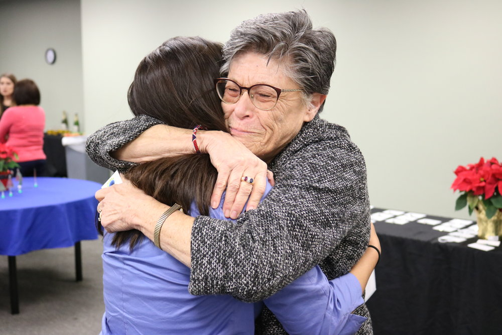 Carol Allbaugh gives Isabella Orozco a giant hug for her moving testimony about IHPC's impact on her life.