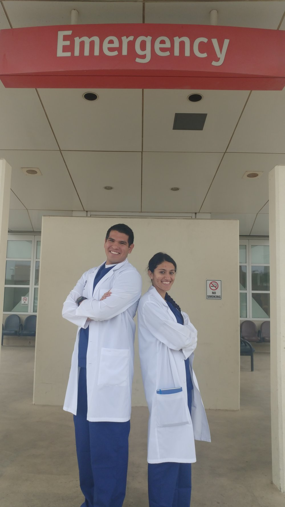 Andrew Hoover and Hannah Abdelmessih pose in their white coats.