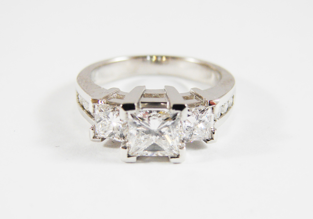 1.00ct princess cut center stone, 1.00tcw diamond side stones, 4 small round diamonds on each of the sides on the shank, platinum ring.  Starting at $12,000 for this stone size and VS clarity FG colour  Can be customizable with any stone, size, metal etc.
