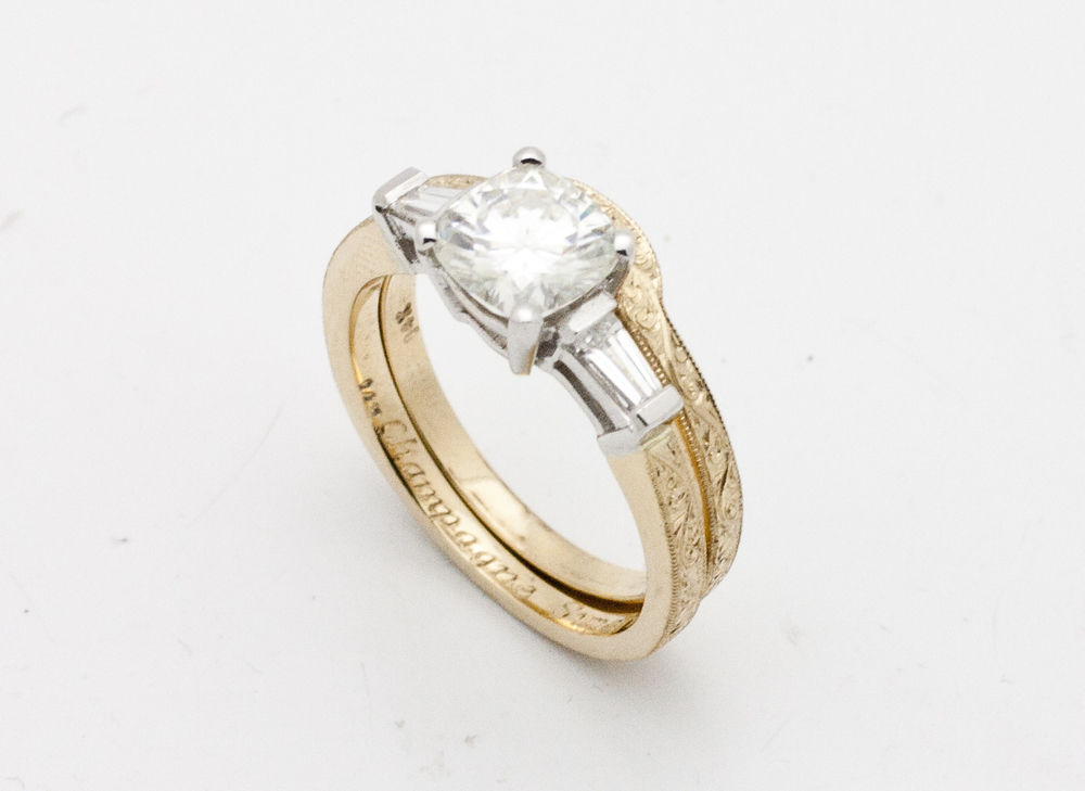 1.15ct round brilliant cut center stone flanked by 0.30tcw tapered baguette diamond side stones, shank set in 18kt yellow gold with a hand engraved band, comes with matching wedding band.  Starting at $9000 for this stone size and quality  Can be customizable with any stone, size, metal etc.