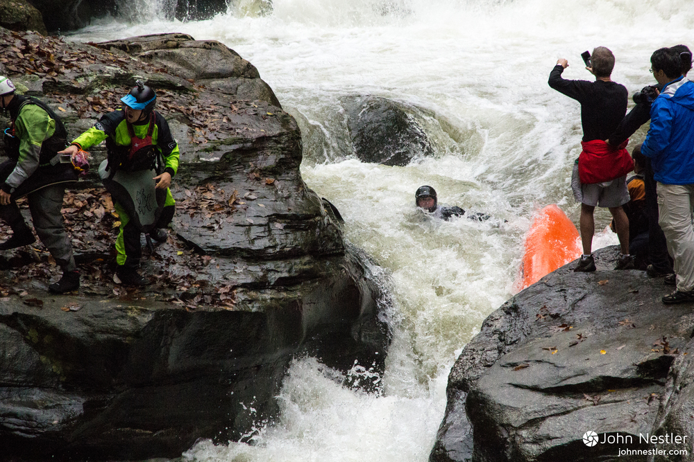 A racer swims through the notch while onlookers scramble to rope him out.