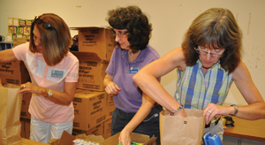 Junior Auxiliary of Taney County members, from left,Brenda Galyean, Donna Harris and Cathy Brown, pack brown paper sacks with ready-to-eat meals, snacks, shelf-stable milk and juice at Hollister Elementary School Thursday evening. Each week, 125 sacks of food will be given out to Hollister students identified as possibly not having enough food to eat.