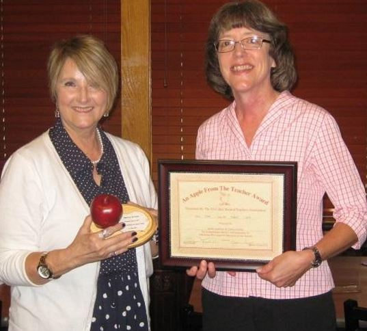 Cathy Brown (right), President of Junior Auxiliary, accepts the Apple from the Teacher award from Evelyn Layton, Vice President of Tri-Lakes Retired Teachers.