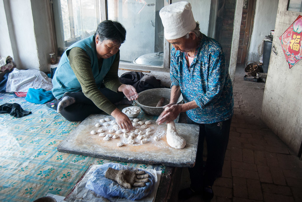 I make the hands in each family's home. As I am mixing soil, the women are kneading dough, preparing our meal. In July 2011, while a rough draft of her hand dried on the  kang,  Zhang Shuzhi (right) and a visiting neighbor rolled out dough for steamed pork dumplings.