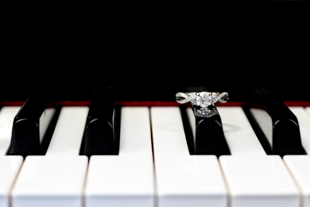 Bride's diamond engagement ring on piano before wedding ceremony