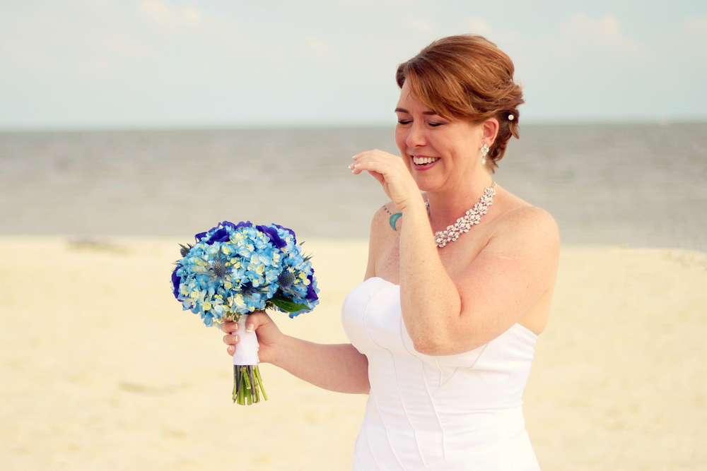 Candid photograph of bride laughing on beach