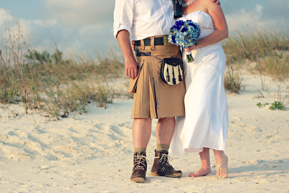 Wedding portrait of bride in dress and groom in kilt with sand dunes on Biloxi Beach