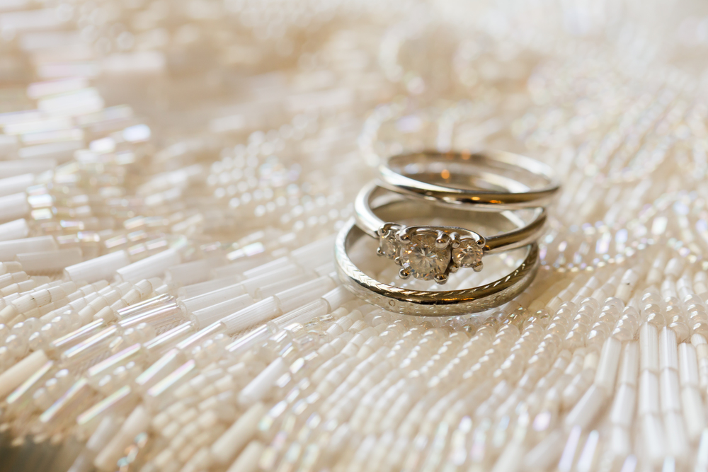 Wedding rings macro photograph on ivory beaded clutch