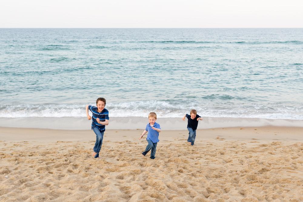 three little boys (brothers) running on beach