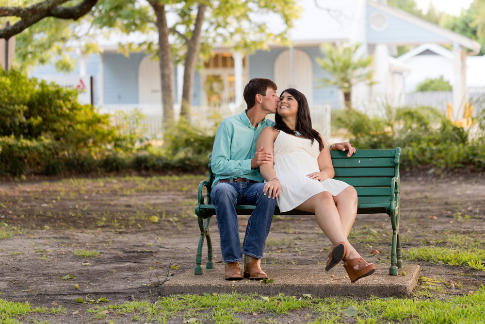 man kissing woman on cheek on park bench (engagement photo)