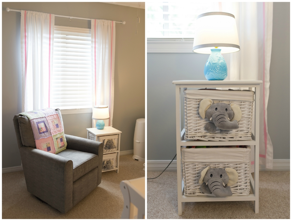 Baby girl nursery with gray glider, pastel quilt, pink curtains, elephant table, blue lamp
