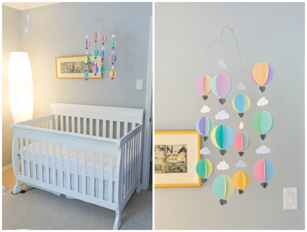 colorful pastel girl baby nursery with white crib, balloon mobile