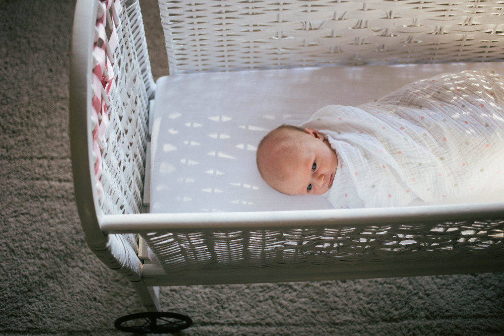 baby girl in wicker bassinet