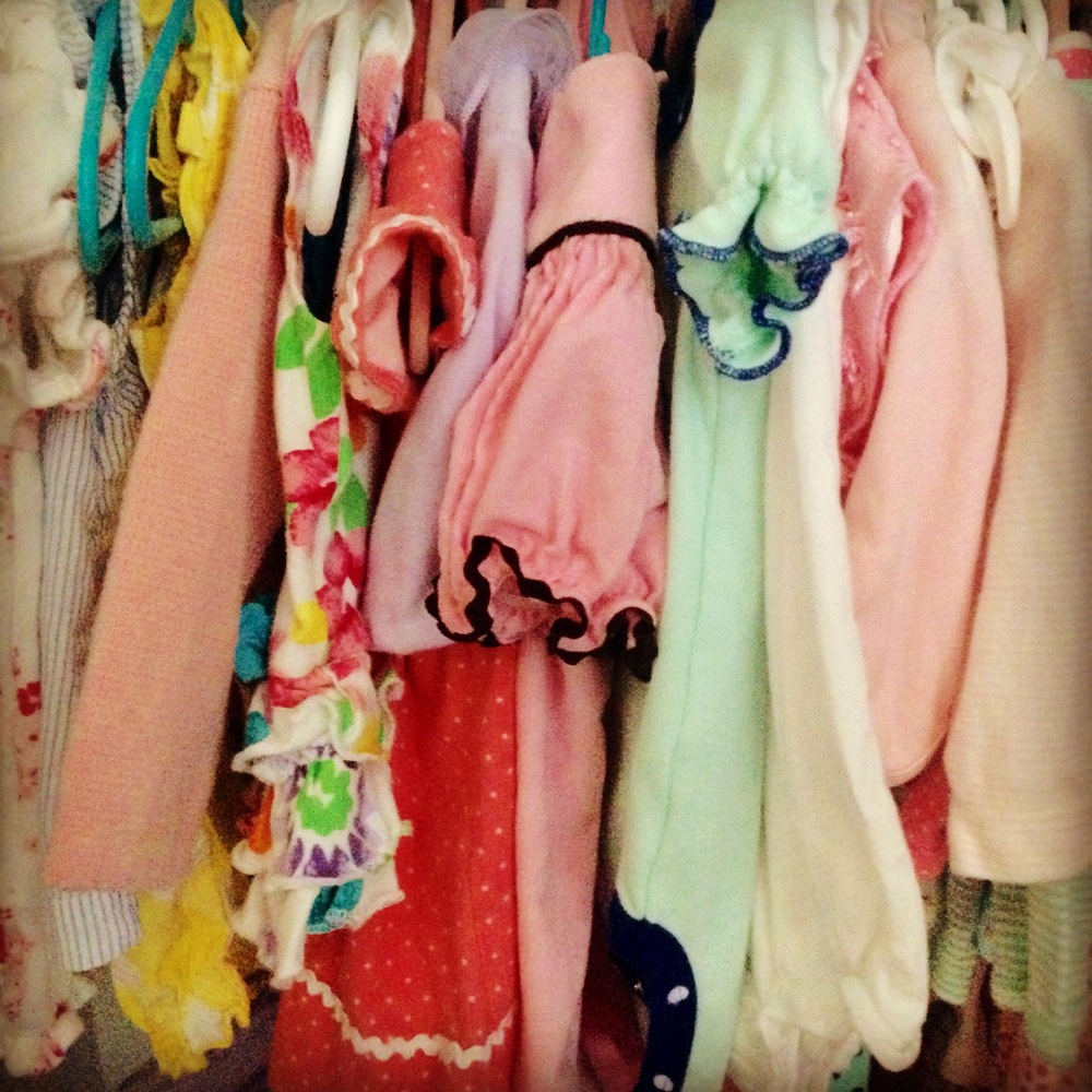 baby girl clothes hanging in closet