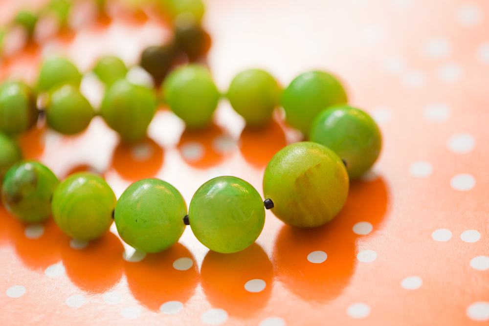 green jade necklace (jewelry macro) with orange and white dot backdrop