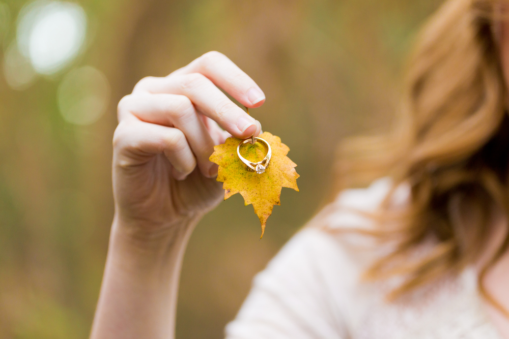 vintage engagement ring with autumn leaf in woods