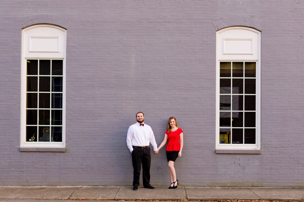 classic red and gray engagement photo in downtown Ocean Springs